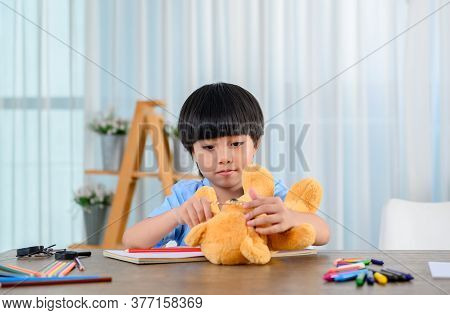 Asian Little Kid Alone At Home And Play With Doll. Son With Toy As Friend. Lonely Boy Unhappy.