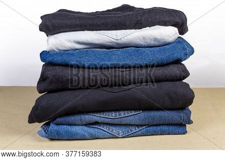 Different Jeans Various Colors Folded In The Stack On Textile Surface