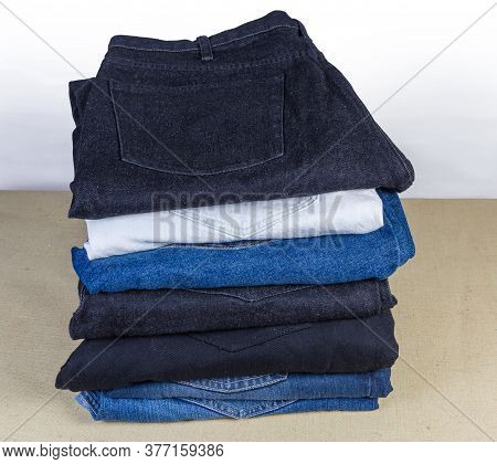Several Different Pairs Of Jeans Various Colors Folded In The Stack On Textile Surface