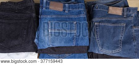 Different Pairs Of Jeans Various Colors And Textures, Folded With Waistbands And Back Pockets Up, To