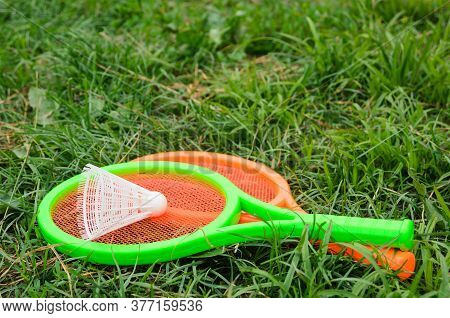 Two Children's Tennis Rackets With A Shuttlecock. Outdoor Activities With Children. Selective Focus.