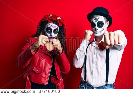 Couple wearing day of the dead costume over red punching fist to fight, aggressive and angry attack, threat and violence