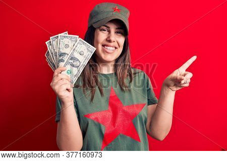 Woman wearing t-shirt with red star communist symbol holding bunch of dollars banknotes smiling happy pointing with hand and finger to the side