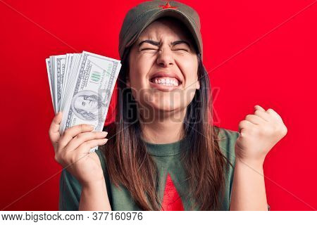 Woman wearing t-shirt with red star communist symbol holding bunch of dollars banknotes screaming proud, celebrating victory and success very excited with raised arm