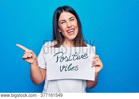 Young beautiful woman asking for optimist attitude holding paper with positive vibes message smiling happy pointing with hand and finger to the side