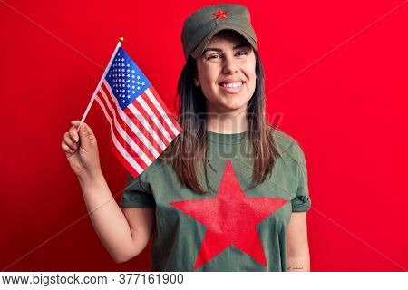 Beautiful woman wearing t-shirt with red star communist symbol holding united states flag looking positive and happy standing and smiling with a confident smile showing teeth