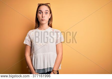 Young beautiful woman wearing casual t-shirt and sunglasses over isolated yellow background puffing cheeks with funny face. Mouth inflated with air, crazy expression.