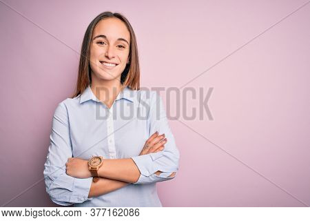 Young beautiful businesswoman wearing elegant shirt standing over isolated pink background happy face smiling with crossed arms looking at the camera. Positive person.