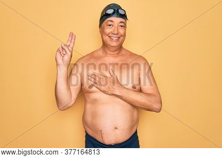 Middle age senior grey-haired swimmer man wearing swimsuit, cap and goggles smiling swearing with hand on chest and fingers up, making a loyalty promise oath