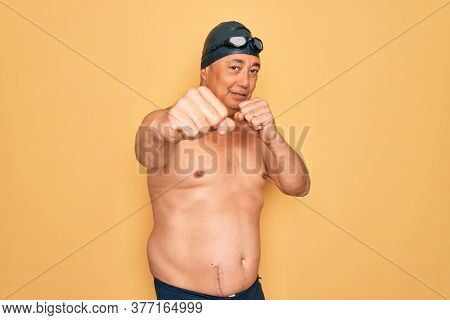 Middle age senior grey-haired swimmer man wearing swimsuit, cap and goggles Punching fist to fight, aggressive and angry attack, threat and violence