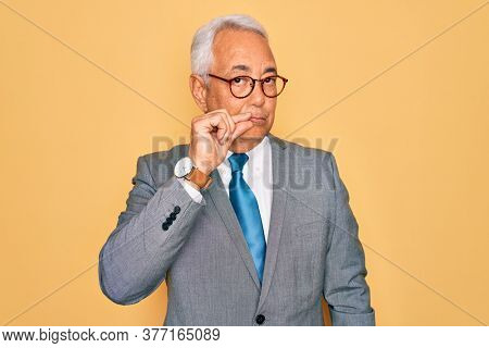 Middle age senior grey-haired handsome business man wearing glasses over yellow background mouth and lips shut as zip with fingers. Secret and silent, taboo talking