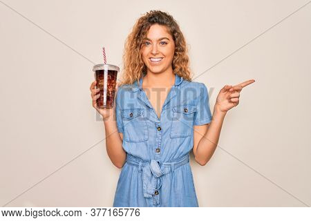 Beautiful blonde woman with blue eyes drinking cola beverage using straw to refreshment very happy pointing with hand and finger to the side