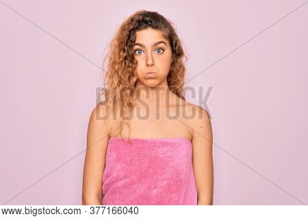 Beautiful blonde woman with blue eyes wearing towel shower after bath over pink background puffing cheeks with funny face. Mouth inflated with air, crazy expression.