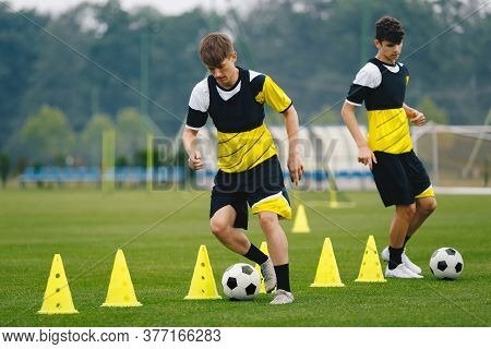 Boys On Soccer Football Training. Young Players Dribble Ball Between Training Cones. Players On Foot