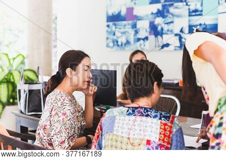 Group Of Woman Guest Checking Hotel Documents At Reception.