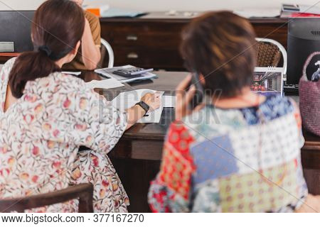 Woman Checking Hotel Document With Receptionist At Hotel.