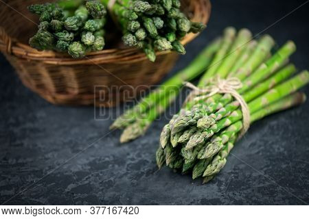 Asparagus. Fresh raw organic green Asparagus sprouts closeup. On black slate table background. Healthy vegetarian food. Raw vegetables, market. Healthy eating concept, diet, dieting. Top view