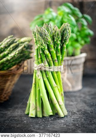 Asparagus. Fresh raw organic green Asparagus sprouts closeup. Over wooden table. Healthy vegetarian food. Raw vegetables, market. Healthy eating, diet, dieting concept.