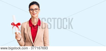 Young beautiful woman wearing glasses holding graduate degree diploma looking positive and happy standing and smiling with a confident smile showing teeth