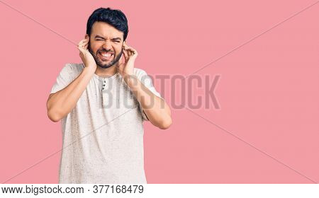Young hispanic man wearing casual clothes covering ears with fingers with annoyed expression for the noise of loud music. deaf concept.