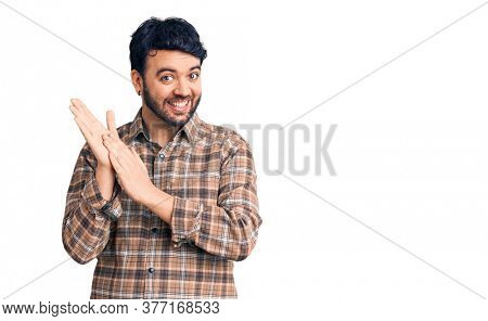 Young hispanic man wearing casual clothes clapping and applauding happy and joyful, smiling proud hands together