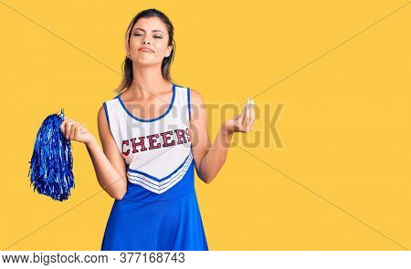 Young beautiful woman wearing cheerleader uniform doing money gesture with hands, asking for salary payment, millionaire business