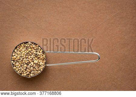 hemp seeds on metal measuring scoop, top view on brown handmade paper with a copy space