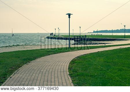 A Winding Footpath Along The Shores Of The Curonian Strait In Neringa. A Couple Walks Along A Path B