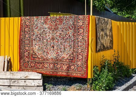 An Oriental Red Carpet With Patterns Dries On A Yellow Metal Fence Near The House. Carpet Cleaning A