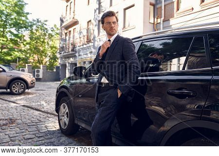 Side View Of Confident Business Man In Formalwear And Eyewear Adjust His Tie, Leaning At The Car And