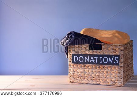 Donation Box For Clothing Donations On A Blue Background. Charity And Donation Concept. Copy Space.