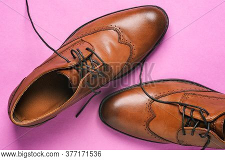 Brown Mens Shoes Close-up. Classic Shoes With Untied Laces On A Pink Background. Shoes For Weddings,