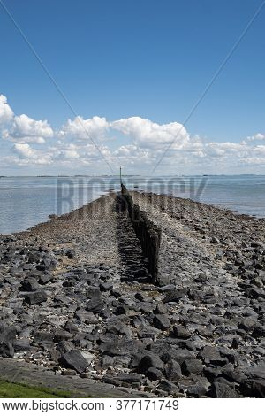 A Dam With Stakes That Goes Into The Water From The Beach With Blue Sky And White Clouds