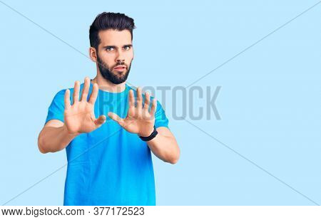Young handsome man with beard wearing casual t-shirt moving away hands palms showing refusal and denial with afraid and disgusting expression. stop and forbidden.