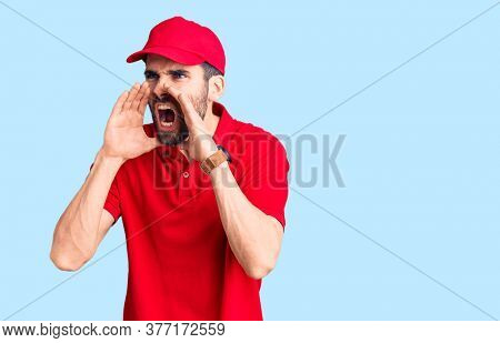 Young handsome man with beard wearing delivery uniform shouting angry out loud with hands over mouth