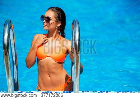 Sexy Girl In Trendy Swimsuit  In Pool. Woman Summer Fashion. Sexy Girl With Fit Body, Lonh Hair, Hea