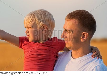 Fair Haired Boy And Young Father Portrait. Countryside