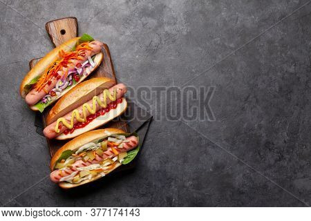 Various hot dog with vegetables, lettuce and condiments on stone background. Top view with copy space. Flat lay
