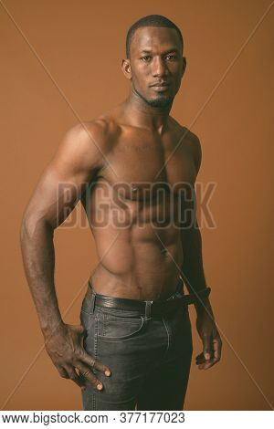 Handsome Muscular African Man Shirtless Against Brown Background
