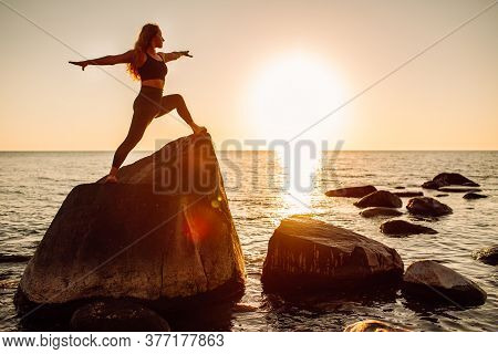 Young Long-haired Woman In Warrior Pose From Yoga Standing On A Big Stone In Water. Sunset, Relaxati