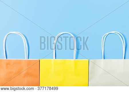 Multicolored Paper Bag On A Light Blue Background. Shopping And Sale Concept. Shop Shopping Concept.