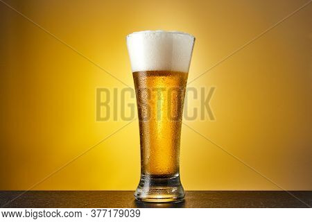 Cold Craft Light Beer In A Glass With Drops On A Dark Table. Pint Of Beer On Yellow Color Background