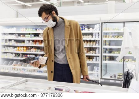 Young Man In The Supermarket In The Department With Frozen Foods. A Brunette In A Medical Mask Durin