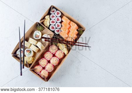 Tasty Sushi Rolls In Disposable Kraft Paper Boxes, Sauce On Dark Table. Concept Delivery Service Jap