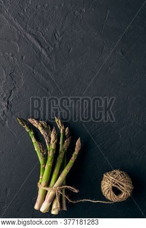 Uncooked Green Asparagus Stems In Bunch Are Tied With Jute Thread On Black Slate Background. Skein I