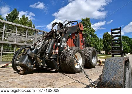 Compact Hydraulic Tractor With Rams Equipped To Attach An Auger Is Chained To A Trailer Bed.