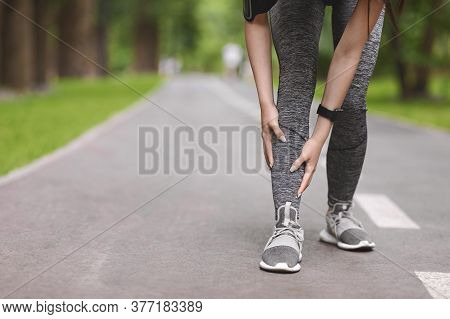 Young Female Runner Suffering From Shin Splints While Jogging In Park, Massaging Painful Area, Havin