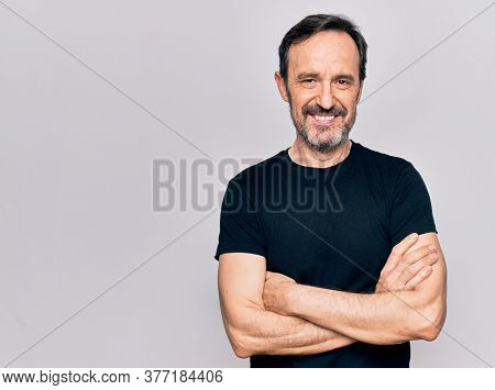 Middle age man wearing casual black t-shirt standing over isolated white background happy face smiling with crossed arms looking at the camera. Positive person.