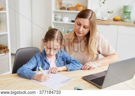 Portrait Of Caring Adult Woman Helping Girl Doing Homework Or Studying At Home While Sitting At Desk