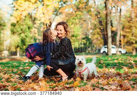 Happy Family Playing With Dog In Autumn Park. Mother And Daughter Having Fun Together On A Walk. Fas